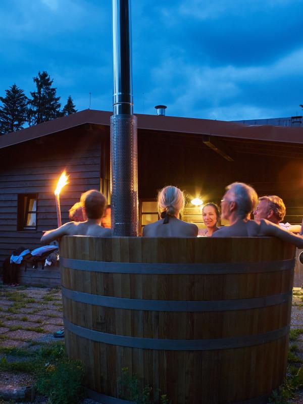 Gäste im beheizten Hot Tub des Almbad Huberspitz während der Abenddämmerung