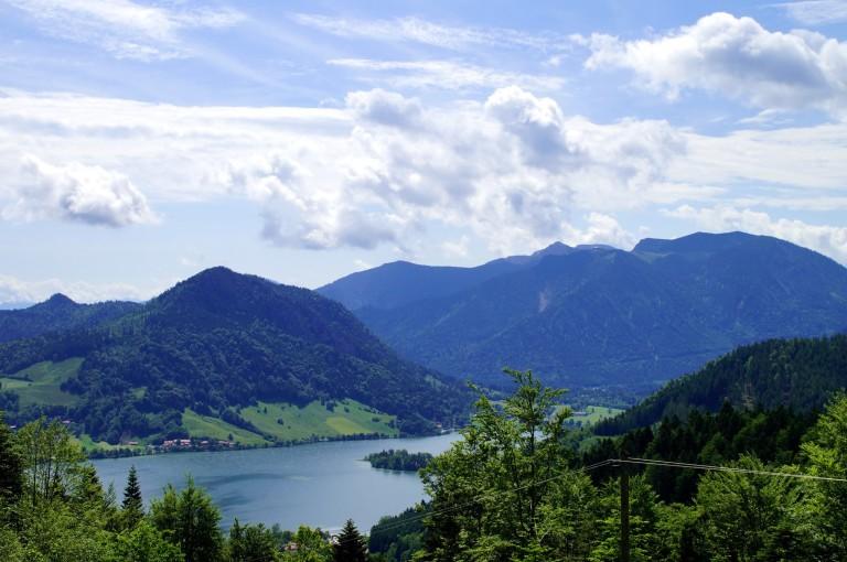 Der zauberhafte Blick auf den Schliersee in Alleinlage auf über 1.100 Meter. Der Schliersee zeigt sich vor Bergpanorama im weiß-blauen Himmel.