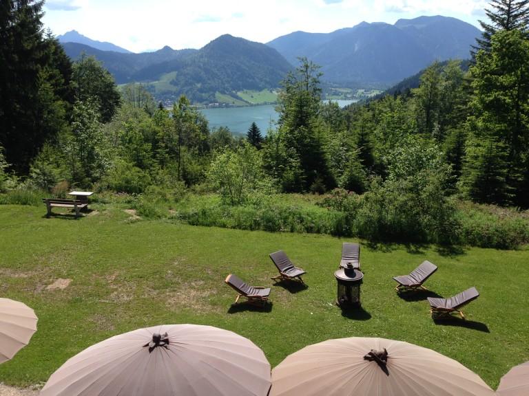 Liegestühle auf der Wiese mit Blick auf den Schliersee, im Vordergrund die braunen Sonnenschirme der Sonnenterrasse