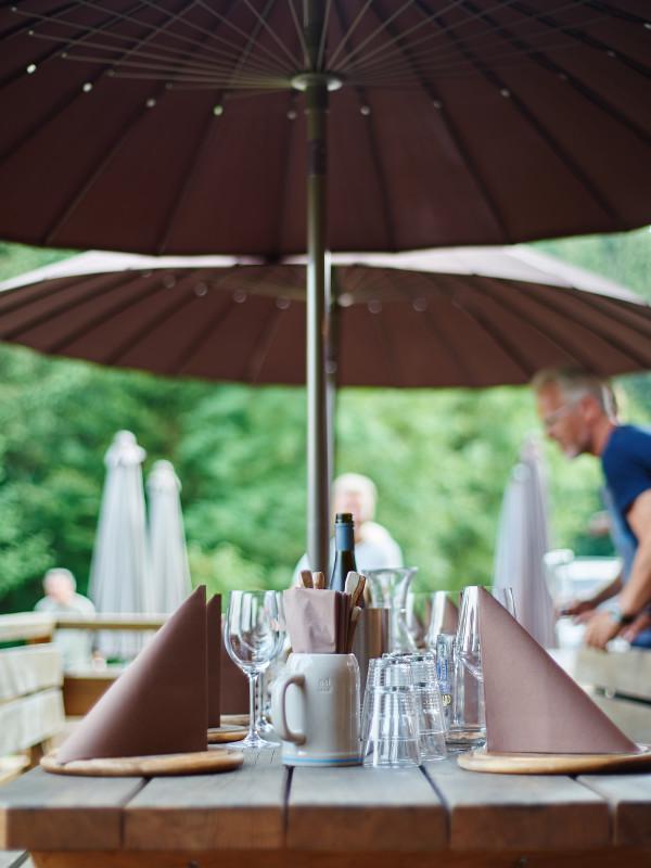 Gedeckter Tisch mit gespannten braunen Sonnenschirmen auf der Terrasse des Almbad Huberspitz