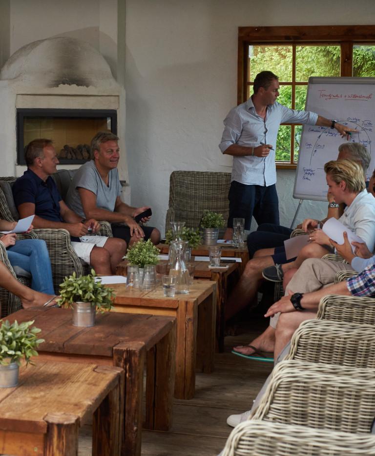 Der Vortragende erklärt anhand eines Flipchart Inhalte, die Tagungsteilnehmer sitzen gemütlich im Wintergarten des Almbad Huberspitz