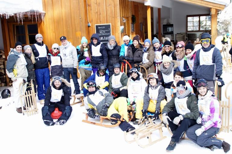 Große Gruppe Schlittenfahrer, posierend im Schnee vorm Almbad Huberspitz
