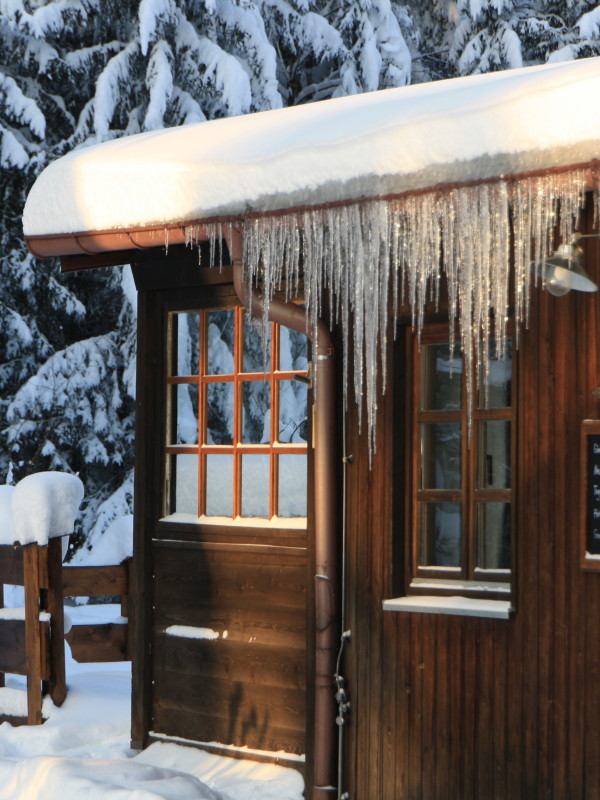 Im Winter: Lange Eiszapfen am Dach des holzvertäfelten Almbad Huberspitz