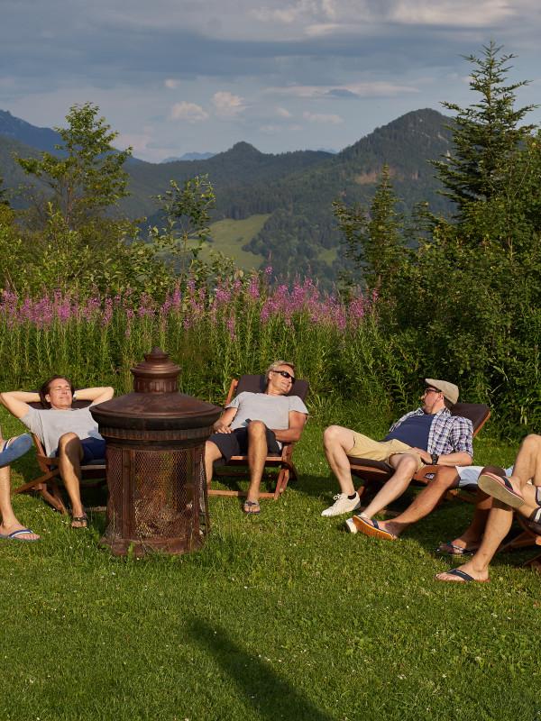 Freunde entspannen im Liegestuhl-Stuhlkreis vor dem sagenhaften Blick auf den Schliersee am Almbad Huberspitz