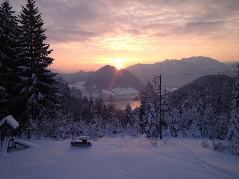 winterlicher Sonnenuntergang hinter dem Bergpanorama und den davorliegenden Schliersee, vom Almbad Huberspitz aus.