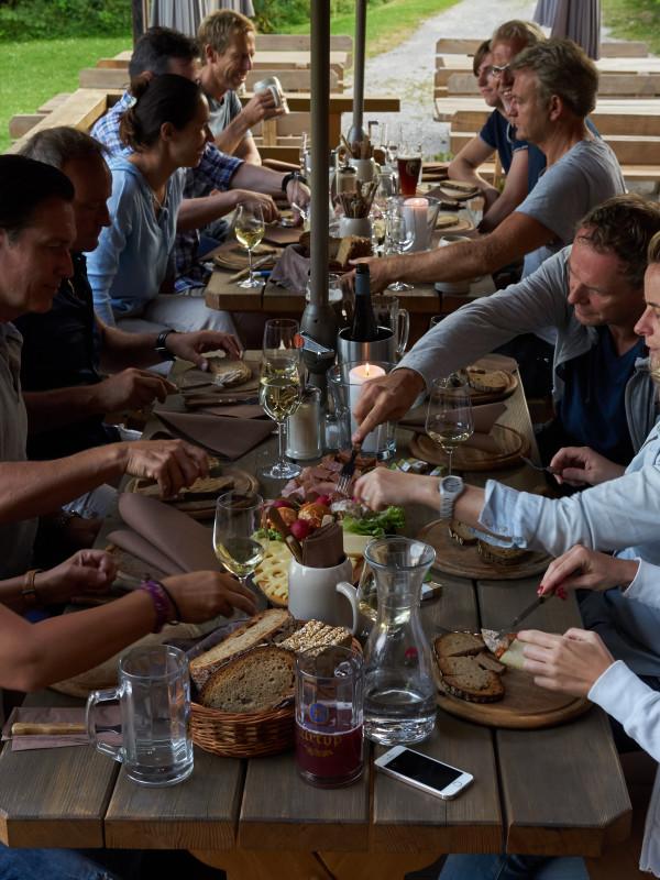 Workshop-Mittagspause auf der Lärchenholzterrasse des Almbad Huberspitz, dabei gibt es BIO-Menü vor atmosphärischer Almwiese mit zauberhaften Blick auf den Schliersee vom Almbad Huberspitz