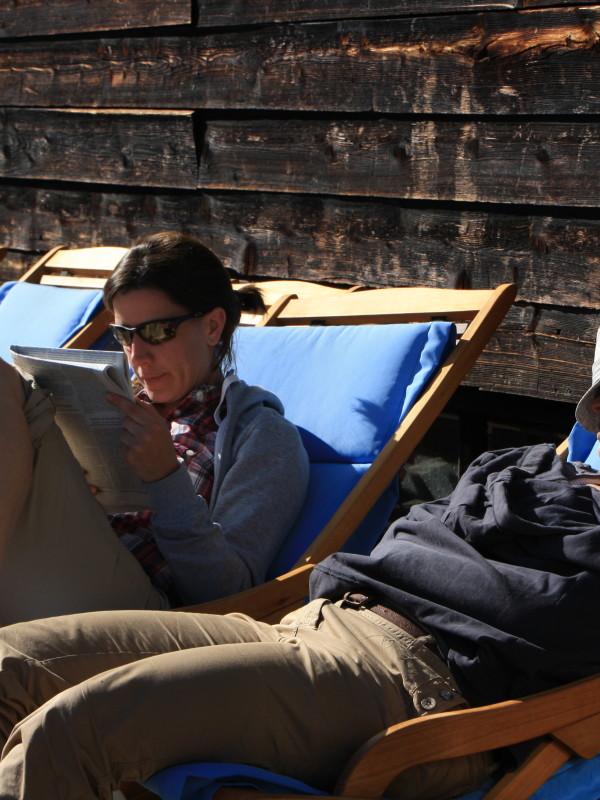 Gäste in Liegestühlen auf der Sonnenterrasse des Almbad Sillberghaus zur Entschleunigung