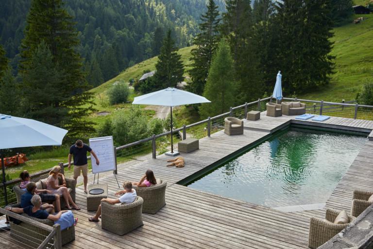Tagungsgruppe am Almpool mit Ausblick zu inspirierender Kulisse mit Almwiesen und Bergpanorama