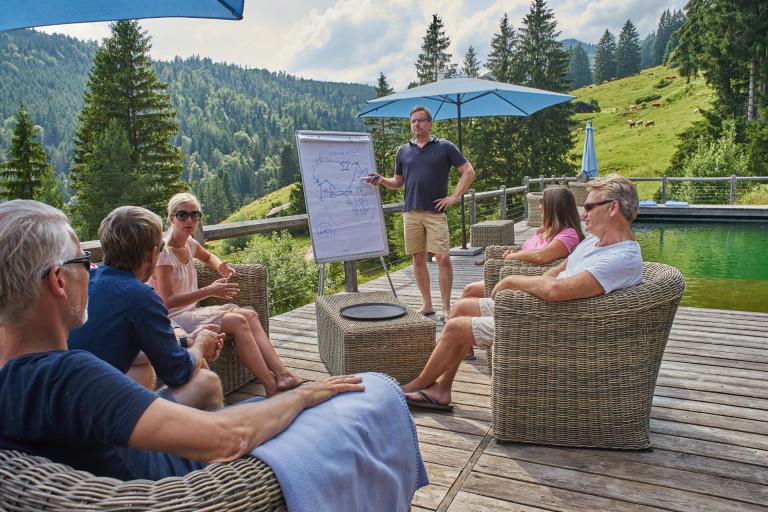 Tagungsgruppe mit Flipchart am Almpool des Almbad Sillberghaus mit Blick zur Almwiese
