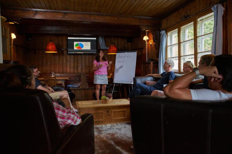 Coach vor Flipchart und TV-Screen im Kaminzimmer des Almbad Sillberghaus