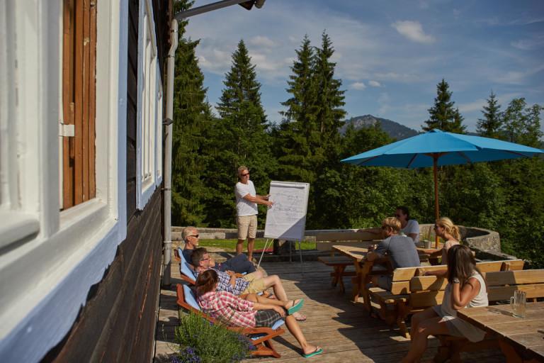 Tagungsgruppe mit Flipchart auf der Sonnenterrasse unter blauen Sonnenschirmen