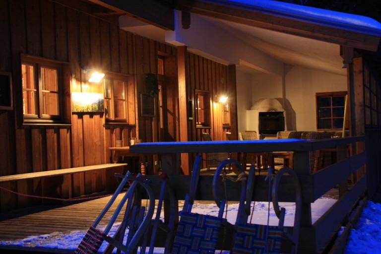 Winterabend: Schlitten lehnen am Geländer zum beleuchteten Almbad Huberspitz