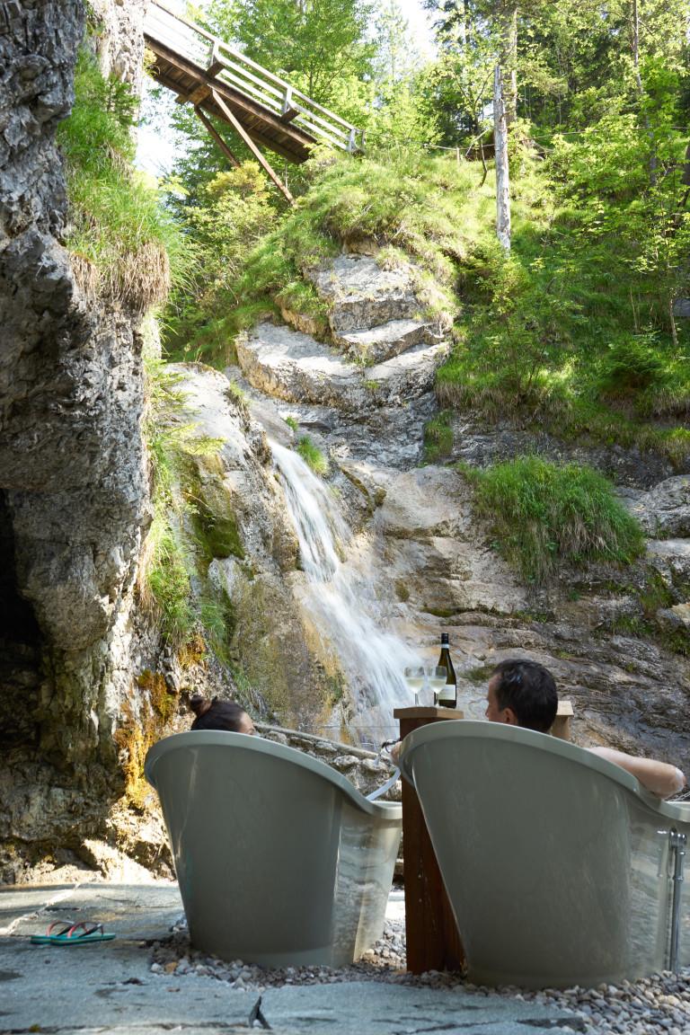 Ein Pärchen in den 2 Badewannen genießen die einzigartige Aussicht auf den Wasserfall des Dorfbad Tannermühl