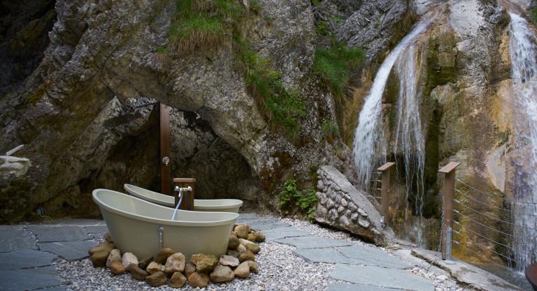 Zwei Outdoor-Badewannen vor einem Wasserfall des Dorfbad Tannermühl