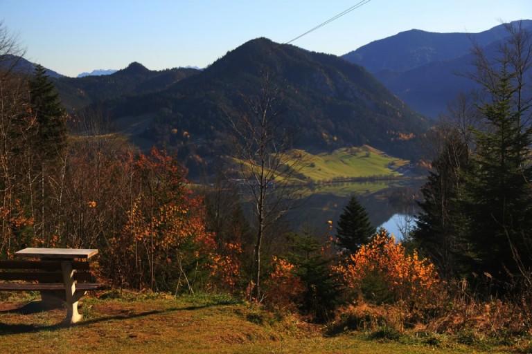 Blick vom Almbad Huberspitz zum Schliersee vor Bergpanorama mit bunten Herbstblättern des Bergwaldes