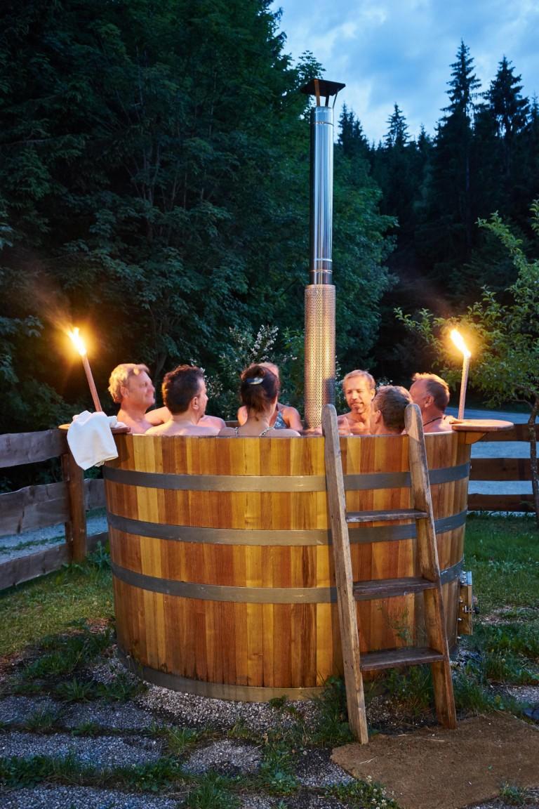 Nach getaner Arbeit erholt man sich im Hot Tub, einem beheizbaren Holzfass, Fackeln leuchten in der Abenddämmerung vor dem Almbad Huberspitz