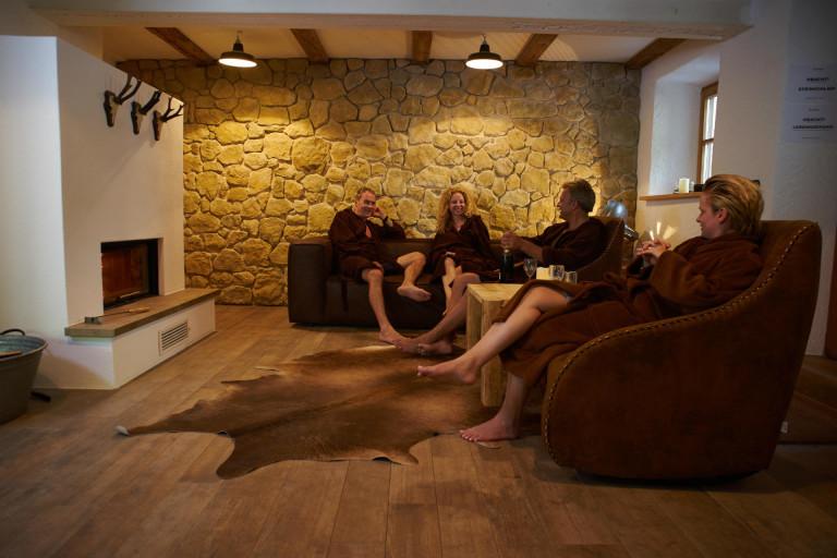 Gruppe entspannt in den Relaxsesseln des schönen Ruheraum mit Feuerstelle im Dorfbad Tannermühl
