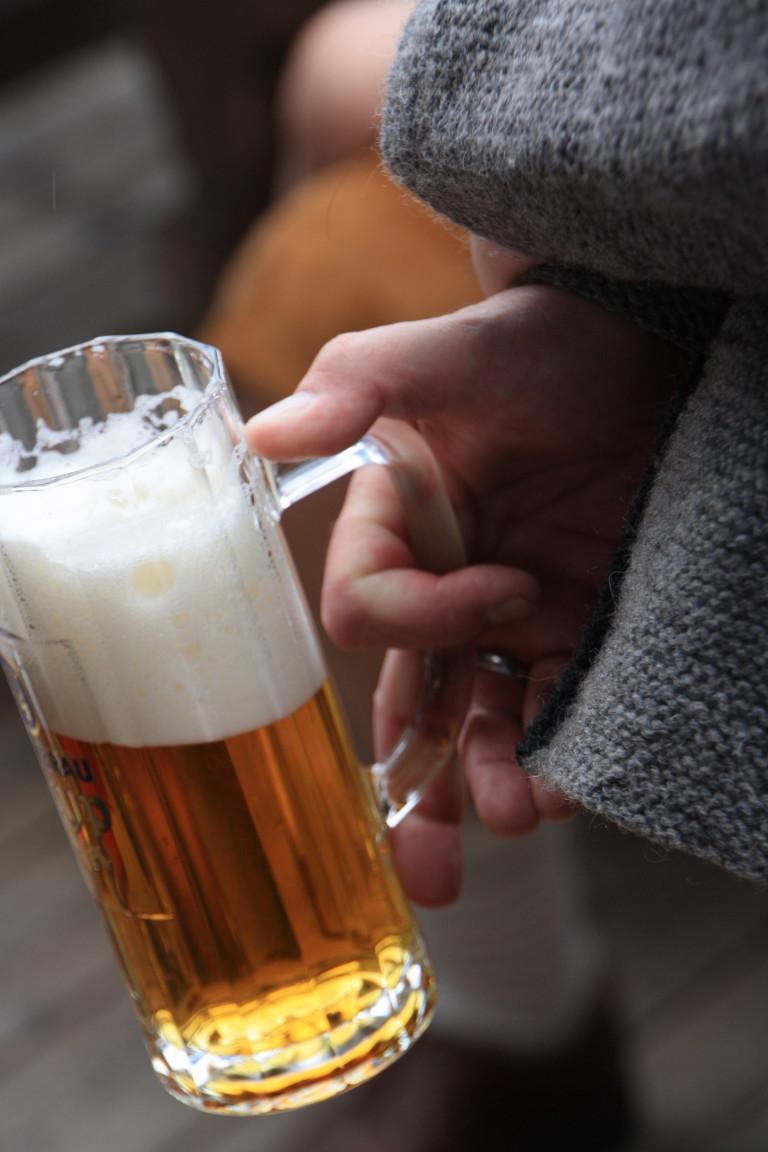 Detailaufnahme: a halbe Bier im Galskrug, locker in der Hand gehalten im Almbad Huberspitz