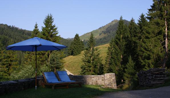 Himmelblaue Liegestühle zum Entschleunigen vor Bergpanorama