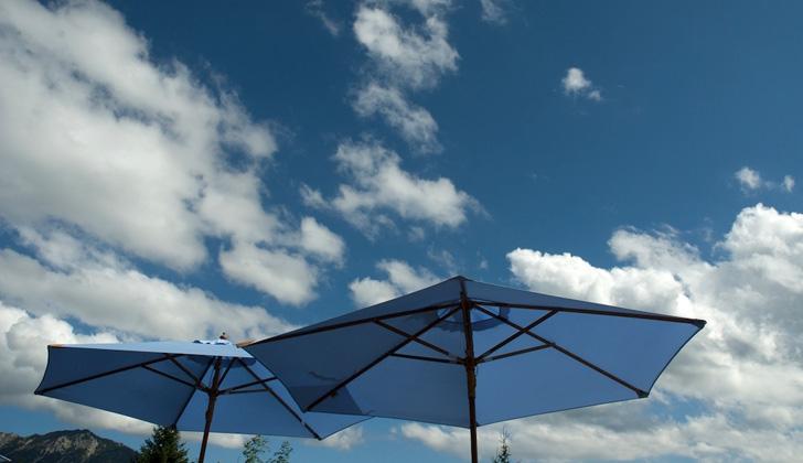 Sonnenschirme mit Sommerhimmel am Almbad Sillberghaus (Foto: almbad.de)