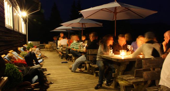 Gäste abends auf der Lärchenholz-Sonnenterrasse des Almbad Sillberghaus