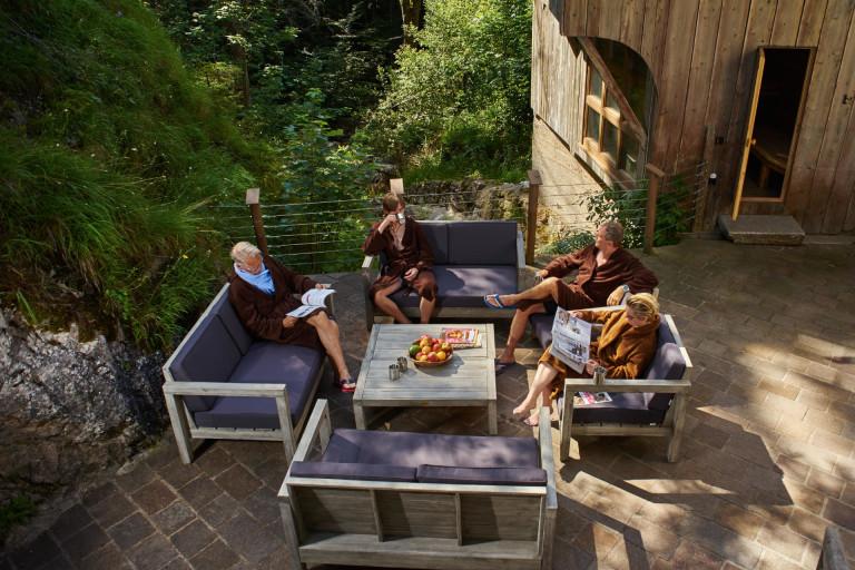 Tagesgäste genießen einzigartige Auszeit im Dorfbad Tannermühl auf der Terrasse des Außenbereichs vor dem Wildbach und der Sauna