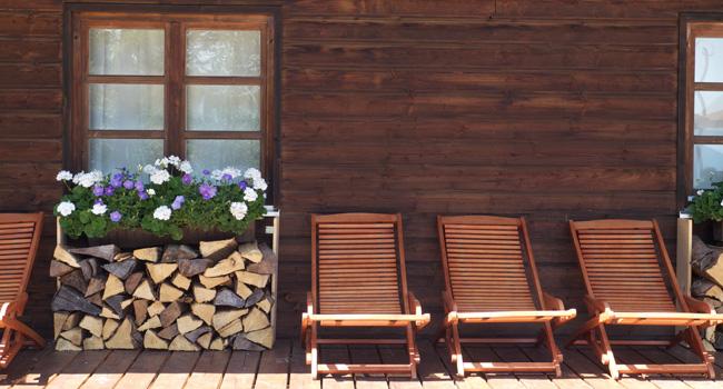 Zwei Liegestühle im Halbschatten, nebst aufgeschichtetem Holz und blühenden Blumen auf der Lärchenholzterrasse des Almbad Huberspitz