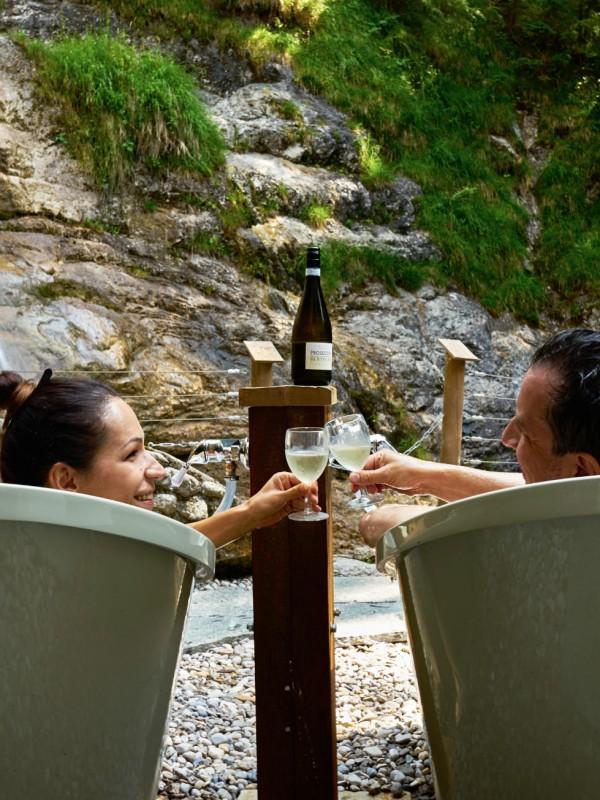 Romantisches Außen-Wannenbad vor dem Wasserfall - ein Paar stößt mit Prosecco an