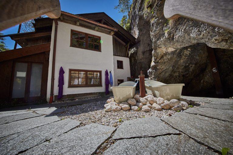 Hausansicht mit Grottendusche und Badewannen