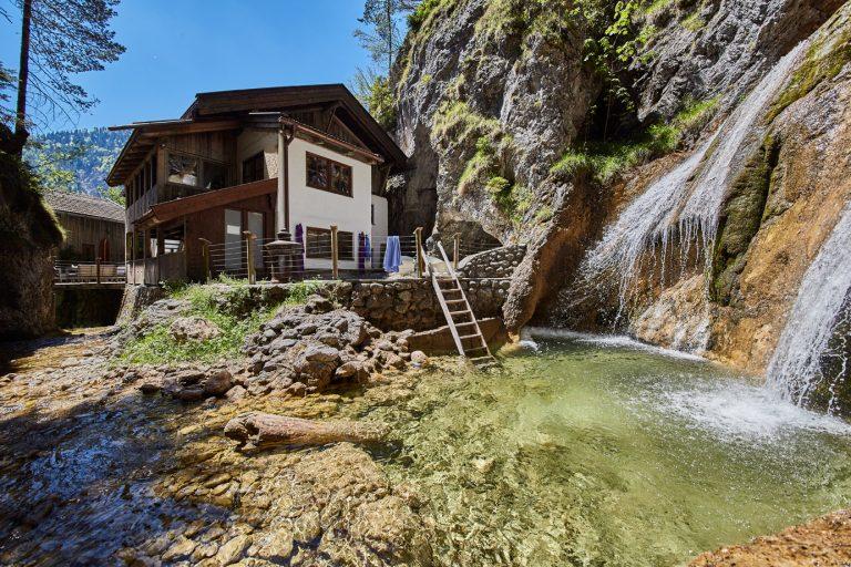 Außenansicht des Dorfbad Tannermühl mit Gumpentauchbecken am Wasserfall, zur Erholung nach Tagungen Seminare & Workshops