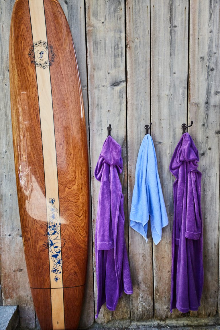 Surfbrett, lila Bademäntel und Handtuch angebracht an der Außenwand der Sauna des Dorfbad Tannermühl