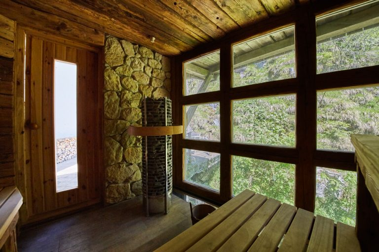 Die Altholz-Stadlsauna des Dorfbad Tannermühl von innen, mit Fensterfront zum Wildbach