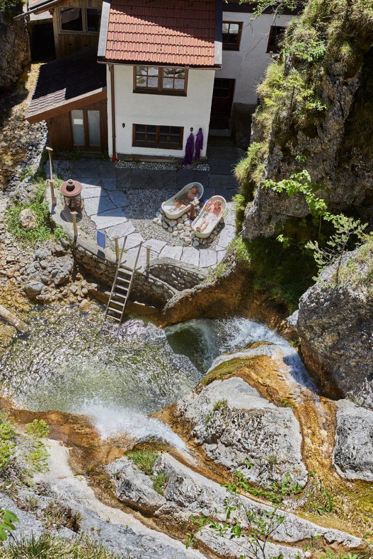 Blick von oben zum Dorfbad Tannermühl mit zwei Outdoor-Wannen am Wasserfall des Dorfbad Tannermühl