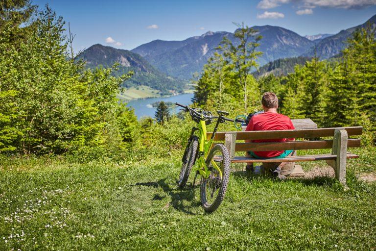 Radlfahrer erholt sich auf der Bank, mit Blick auf den Schliersee, sein Mountainbike an der Bank angelehnt