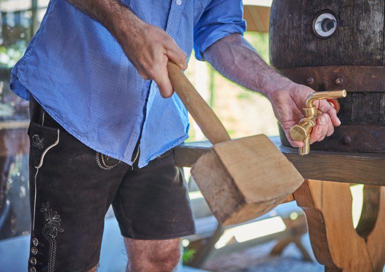 Servicemitarbeiter mit blauem Hemd, schlägt mit Holzhammer zum Bierfass-Anstich im Almbad Huberspitz