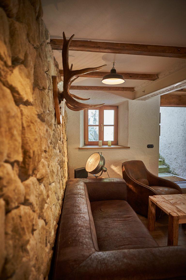 Blick zum Ruhebereich im Kaminzimmer des Dorfbad Tannermühl mit Steinwand und Ledercouch