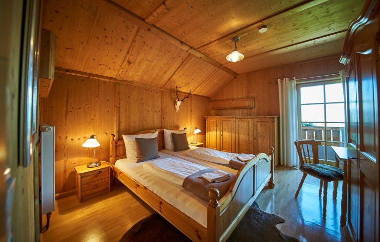 Eines von 10 gemütlichen Gästezimmern zur Übernachtung im Almbad Huberspitz, gemütlich in Holz gehalten und liebevoll gestaltet