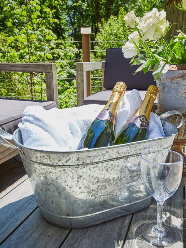 Kühl gestellter Champagner und Rosenstrauß auf dem Tisch der Sonnenterrasse für besondere Anlässe im Dorfbad Tannermühl