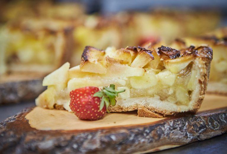 Fruchtiges Stück hausgemachter Apfelkuchen, serviert mit Erdbeere auf einer Holzscheibe - für die Nachmittagspause