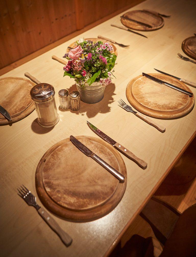 Gedeckter Tisch mit Holzteller, Besteck und kleinem Tisch-Blumenstrauß zur gemütlichen Brotzeit im Almbad Huberspitz