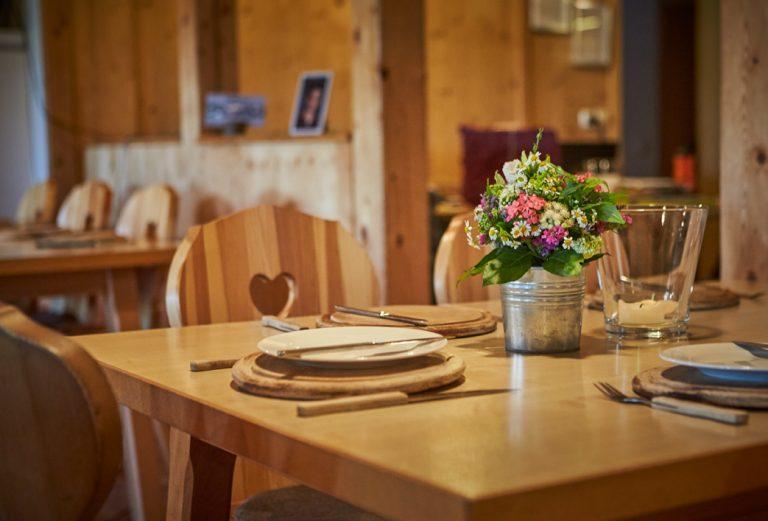 Gedeckter Tisch in der Stube des Almbad Huberspitz mit kleinem Tisch-Blumenstrauß