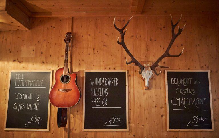Holzvertäfelte Hüttenwand im Loungebereich des Almbad Huberspitz, dekoriert mit Angebotstafeln, Geweih und Gitarre