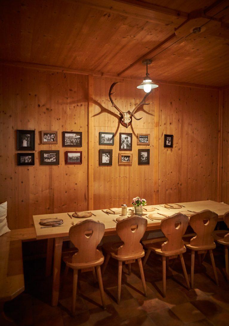 Gemütliches Hüttenflair: Herzerl-Stühle, Bilder aus alten Zeiten und Geweih an der Holzwand der kleinen Stube im Almbad Huberspitz