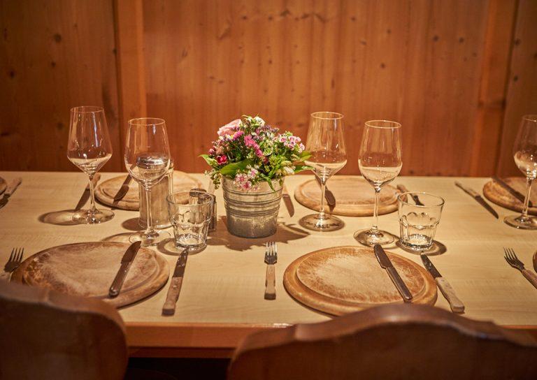 Alles steht bereit, der Tisch ist gedeckt mit Gläsern, Tellern und Besteck, in der Mitte ein kleiner Blumenstrauß