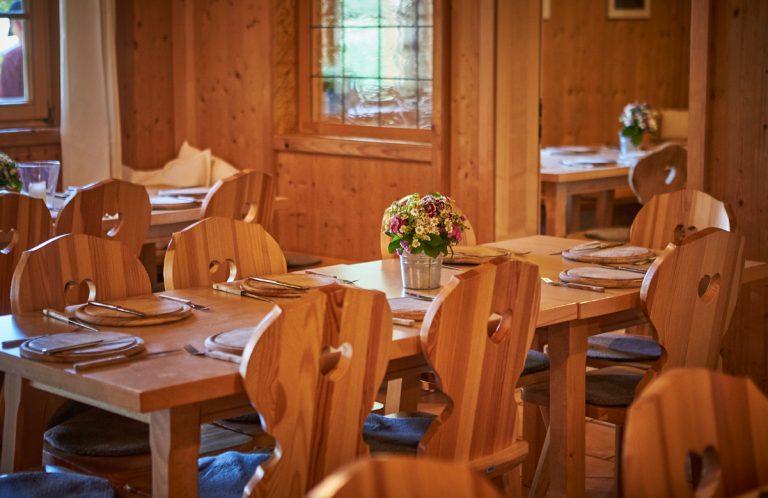 Gedeckte Tische in der Kaminstube mit Herzerlstühle, Holzteller und Blumengesteck im Almbad Huberspitz