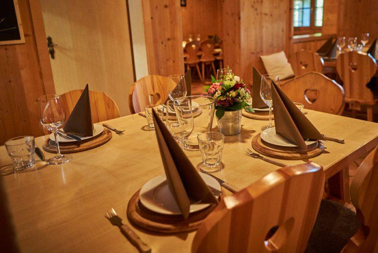 Eingedeckter Tisch im Almbad Huberspitz mit braunen Servietten, kleinen Blumensträußchen