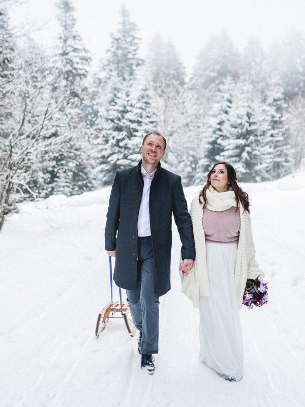 Brautpaar spaziert mit Schlitten durch die verschneite Winterlandschaft beim Almbad Huberspitz