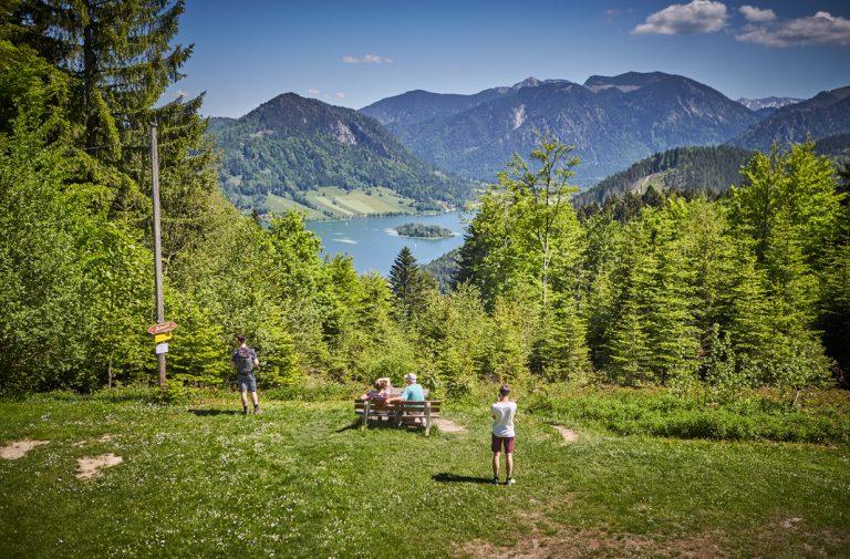 Wanderer genießen den Ausblick im Grünen am einzigartig gelegenen Almbad Huberspitz, hoch über- und mit sagenhaften Blick auf den Schliersee und die dahinter liegende Bergkulisse