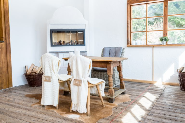 Unter dem Trautisch liegt ein Fell, die Stühle des Brautpaars sind mit 2 Hussen, Mr & Mrs Schilder dekoriert zur standesamtlichen Trauung vorm Kamin im Almbad Huberspitz Kamin im Almbad Huberspitz
