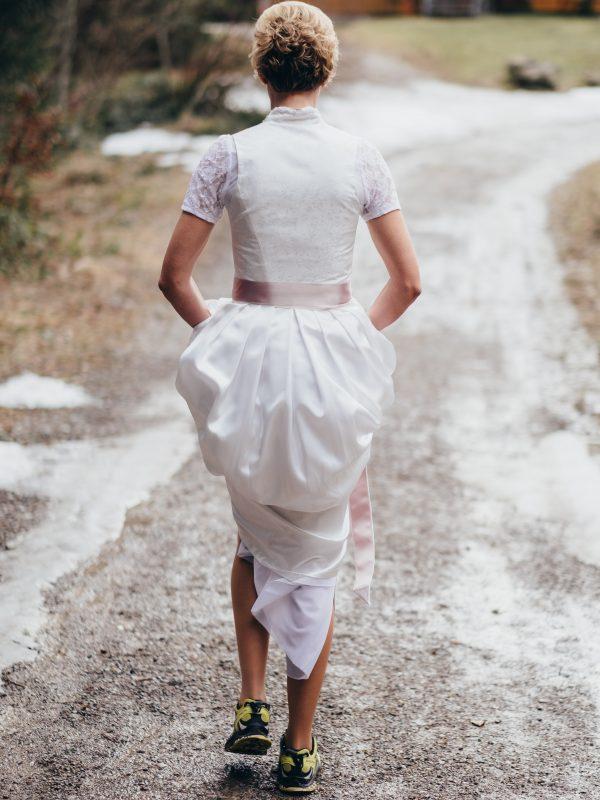Braut im weißen Brautkleid und Sneaker durch den Naturweg vom Almbad Huberspitz runter ins Tal